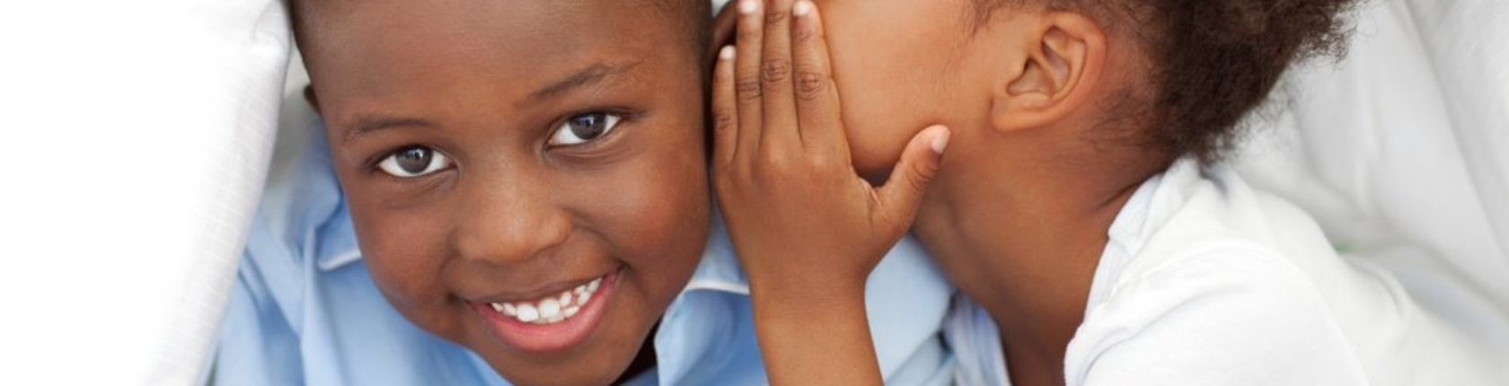 Cute little girl whispering something to her brother under the cover-932272-edited.jpeg