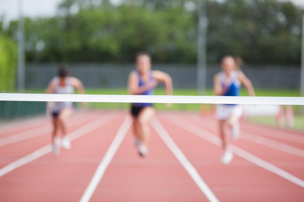 Female athletes running towards finish line on track field